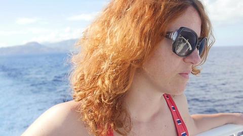 thoughtful woman on a ship: the ship's wake, sea, wind, summertime, summer, sun Footage