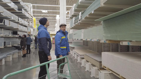 Men in a hardware store choose lumber and boards for repair Live Action
