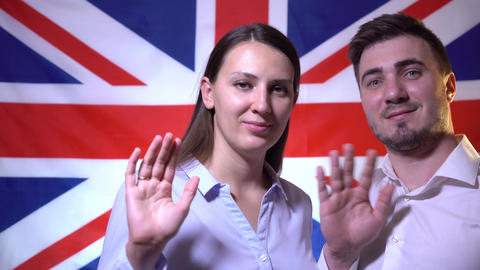 Happy british family handsome man and woman on british flag background, smiling Live Action