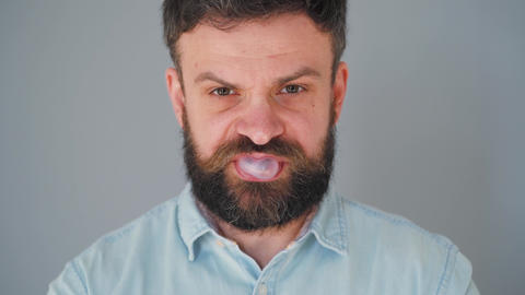 Bearded man chewing chewing gum. Man blowing out a bubble of bubble gum Live Action