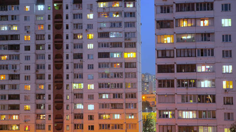 Time lapse of apartment windows at dusk to night with people living in buildings Live Action