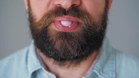Close-up of a bearded man's mouth chewing chewing gum. Man blowing out a bubble Live Action