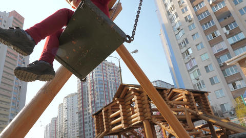 Wooden playground near skyscrapers. Boy in red suit swinging on wooden swing Live Action