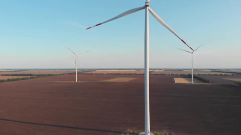 Wind turbines power plant aerial sunset view clear sky green energy Wind mills rotating generating Live Action
