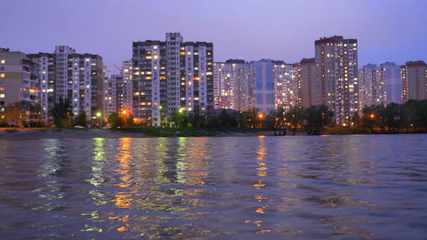 Apartment buildings located near the lake, during sunset with purple sky reflecting in the water. Live Action