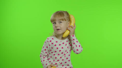 Happy child girl kid imitating telephone conversation with banana isolated on Live Action