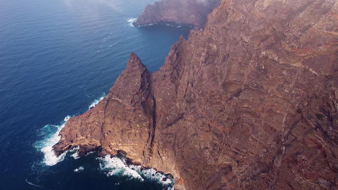 Flying over a scenic landscape, cliffs and ocean in a remote volcanic landscape Live Action