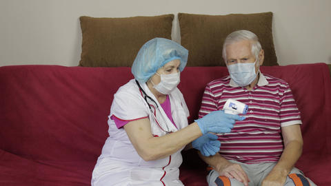 Nurse measures temperature with non-contact electronic thermometer of sick Live Action