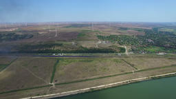 Aerial flight above green meadows and Danube river with windmills on background Footage