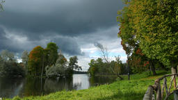Clouds piling up, lush green trees and grass on shore of small lake Footage