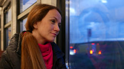 Woman look out train window, optimistic mood, ride at evening through suburbs Footage