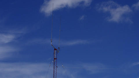 Home based dual spike Telecommunications antenna tower with clouds clearing the  Footage