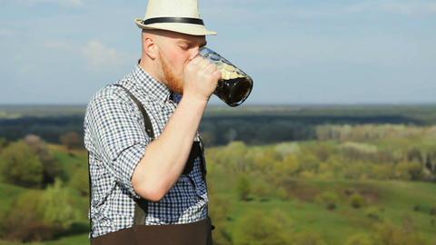 A man in a spring day enjoying a delicious dark beer GIF