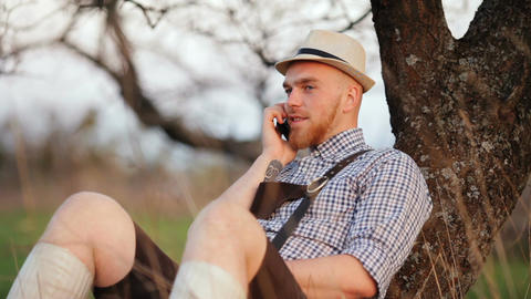 Man outdoors sitting on grass talking on a smartphone Footage