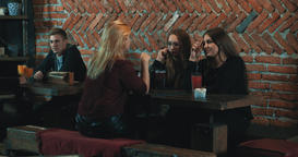 People sitting at bar tables 4k video. Women man friends Footage