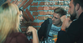 Friends sitting and talking at bar 4k video. Table with beverage Footage
