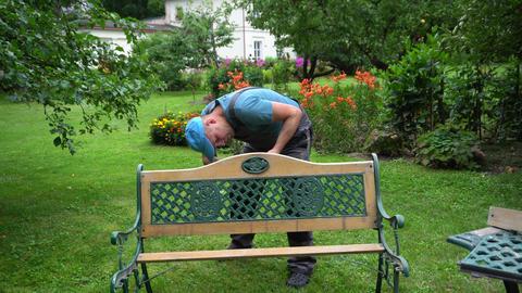 Gardener man disassemble retro bench in garden yard. Outdoor furniture renew Live Action