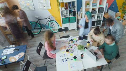 Zoom-out of creative team of designers doing work in modern office working Live Action