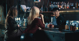 Women friends talking at bar counter 4k video. Bartender making cocktails tricks Footage