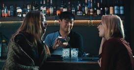 Asian bartender barman making cocktails for two girls at bar counter 4k video Footage