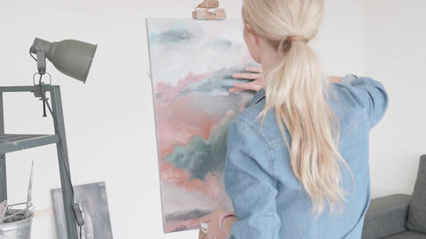 Girl paints the sky with oil paints on canvas. Woman paints with a finger Live Action