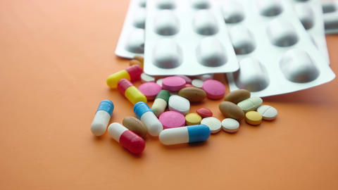 close up of colorful pills spilling on color background Live Action