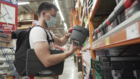 Man choosing right tool box in a hardware store. The buyer in the hardware store Live Action