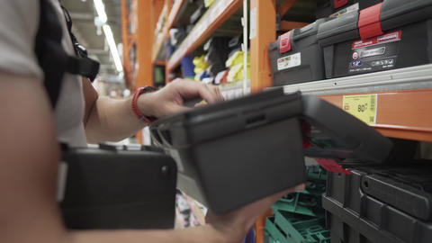 Man wearing protective face mask choosing tool box at hardware store. Male buyer Live Action
