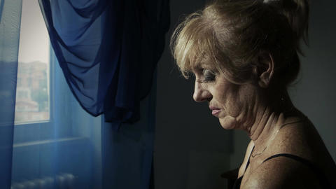 thoughtful woman deep in her problems with window light: depression, desperation Live Action