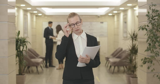 Portrait of strict mid-adult businesswoman in eyeglasses posing with documents Live Action