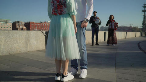 A young couple dancing to live music on the street. Musicians play, and a young Live Action