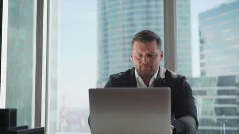Businessman worries while sitting at a laptop. Businessman upset because dollar Live Action