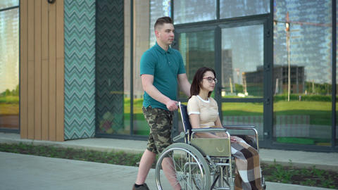 A young man carries a young woman in a wheelchair. An assistant carries a Live Action