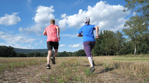 Guy and girl running on the harvested field. Sports healthy lifestyle. Running athletes enjoy run Live Action
