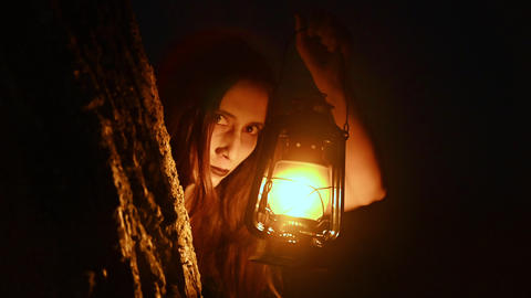 Scary woman with a lantern in night scene - Spooky image of a scary woman with Live Action