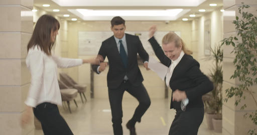 Group of cheerful business people dancing in business center hall and throwing Live Action