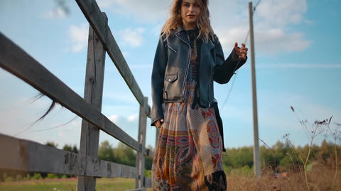 Stylish lady walking near fence in countryside Live Action