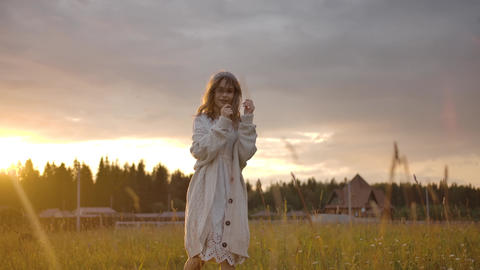 Cheerful romantic woman walking in field during sunset Live Action