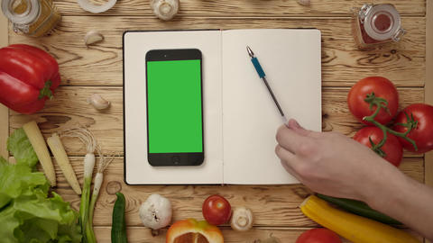 Crop cook pointing with pen at lines in empty diary while cooking with online Live Action