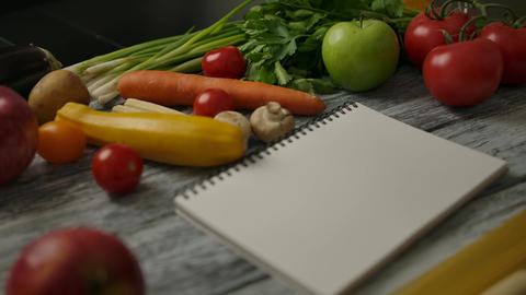 Blank notepad for recipe amidst vegan food on table Live Action