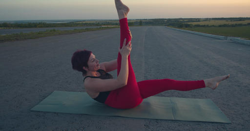 Woman with short hair is doing yoga outdoors in the morning, healthy lifestyle Live Action