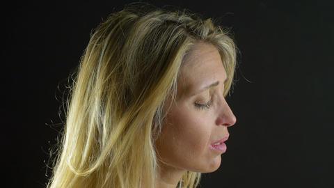 beautiful blonde girl deep in prayer is seeking help of God: crying, praying Footage