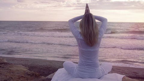 Silhouette young woman practicing yoga on the beach at sunset: meditation Footage