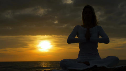 young woman practicing yoga at the sunset near the sea Footage