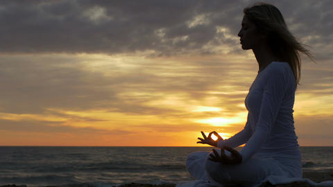 Silhouette of a woman meditating at the beach at sunrise Footage