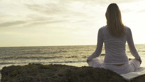 practice of yoga on the beach: woman having meditation moments, spiritual time Live Action