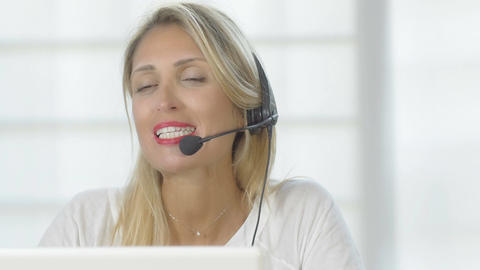 Smiling beautiful woman working in a call center: cute girl at work. 4k Footage