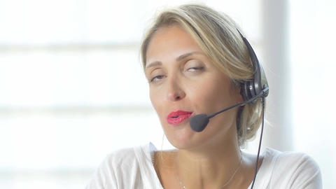 Female customer support operator with headset and smiling. 4K Footage