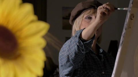 woman painting with sunflower in foreground Footage