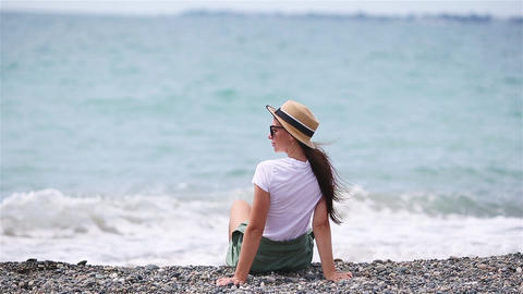 Woman laying on the beach enjoying summer holidays looking at the sea Live Action